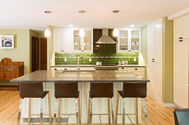 green kitchen island with bar stools